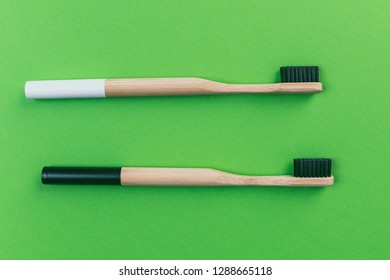 Two bamboo toothbrushes isolated on green background