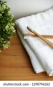 Two bamboo toothbrushes on white towel