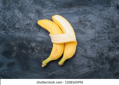 Two bananas isolated on dark background. Concept of embracing couple in love and tenderness