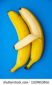 Two bananas on a blue background. One banana embracing the other. The skin of a banana resembles a hand. The concept of gay relationships. LGBT family. Studio photo shot.
