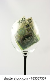 Two banknotes one hundred Polish zlotys inside the wine glass