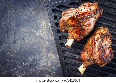 Two Barbecue Leg of Lamb as top view on cast iron grillage