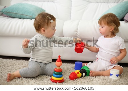 Two barefoot kids sit on carpet and play with colored toys near sofa. Focus on left kid. Shallow depth of field.