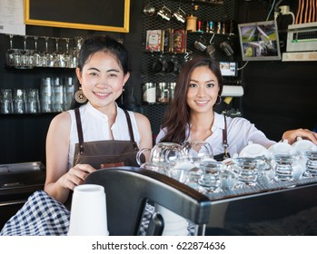 Two Barista smiling and standing in coffee shop counter - young Asian women small business owner working in food and drink cafe
