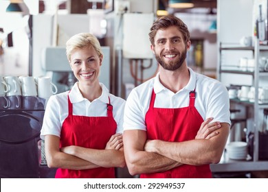 Two baristas smiling at the camera at the cafe