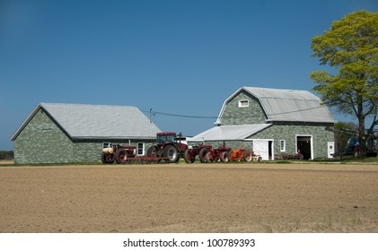 Two barns with farm equipment and a recently plowed field