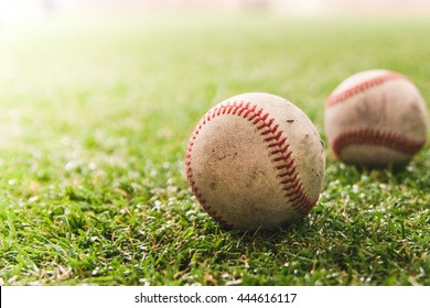 Two baseballs on green artificial turf with vignette and intended grain effect