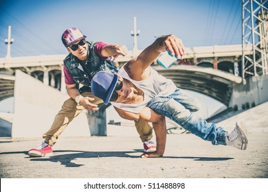 Two bboys doing some stunts - Street artist breakdancer taking an acrobatic selfie outdoors