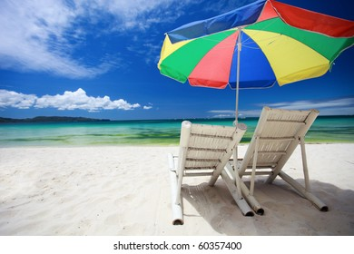 Two beach chairs and colorful umbrella on perfect tropical beach