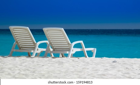 Two beach chairs on a Caribbean beach with the turquoise sea in the background, Curacao