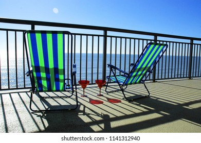 Two beach chairs on a oceanfront deck.