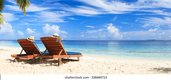 Two beach chairs on the tropical sand beach, panorama ideal for banners