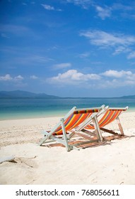Two Beach chairs on the tropical island beach. On the island there are beach chairs, white sandy beaches, bright blue waters, turquoise waters and white clouds.