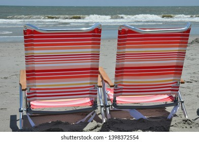 Two beach chairs at the shoreline.
