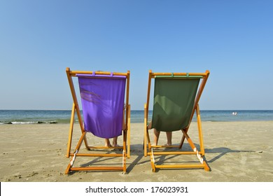 Two beach chairs stand alone on the beach facing the water.