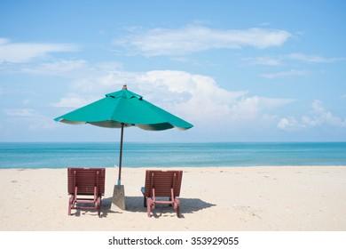 Two beach chairs with sun umbrella on beach