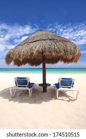Two beach chairs under a palapa thatched sunshade overlooking a tropical beach, Cozumel, Mexico. Copy space available.