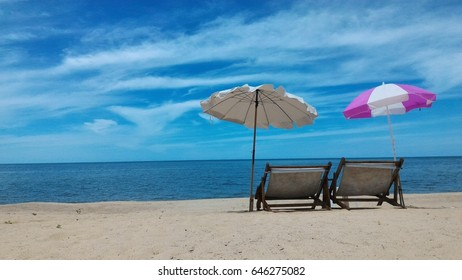 Two beach chairs under white and white and pink umbrellas on a beach with the sea in the background