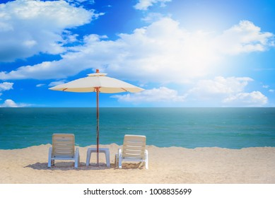 Two beach chairs and white umbrella with blue sky background on the tropical beach at daytime