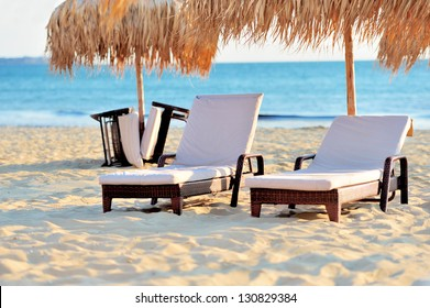 Two beach chairs with white umbrella