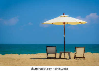 Two beach chairs and white umbrella on the tropical beach at daytime
