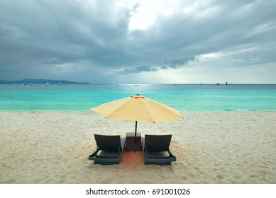 two beach chairs and yellow umbrella on the beach on a cloud day. Beautiful sunlight in rain season on island Boracay, Phillipines.
