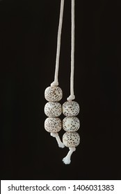 Two beads with cord drooping down,Strings of organic jewelry called rudraksha beads that are the material of malas,which is a rosary or used for prayer(japa)