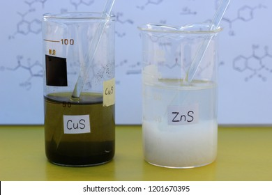 Two beakers with sediments: black copper sulfide, white zinc sulfide.