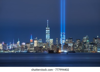 The two beams of the Tribute in Light with skycrapers of Lower Manhattan at night from New York Harbor. Financial District, New York City