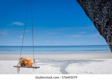 two bear dolls on the swing on the beach , select focus the one bigger