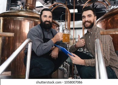 Two bearded brewers cooked lager at brewery of craft beer. Bearded brewer tasting beer. Expertise of beer quality. Quality control.