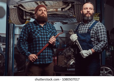 Two bearded brutal mechanics repair a car on a lift in a garage.