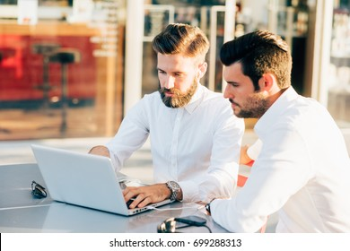 two bearded business men young outdoor using computer - remote working, business, finance concept