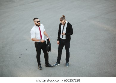 Two bearded businessman working on the street