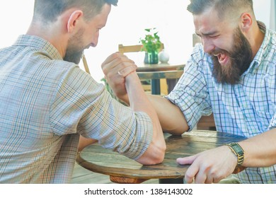 Two bearded hipster men compete arm wrestling. Armwrestling as symbol of competition rivalry confrontation and fighting for leadership success.