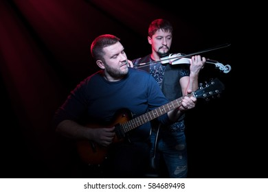 Two bearded men playing on electric guitar and electro violin on a black background