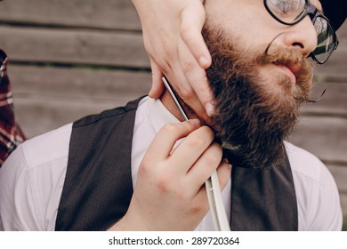 two bearded men shave outdors