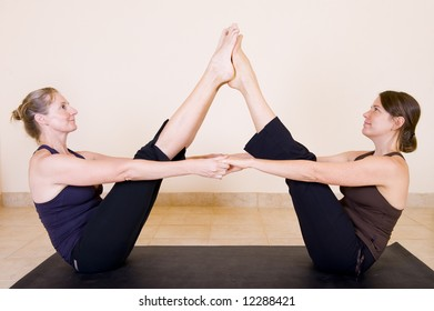 Two beautiful adult ladies in the yoga 'Boat pose - Navasana', facing each other and holding hands.