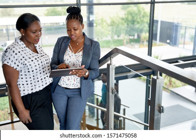 Two beautiful African American businesswomen in bright modern of