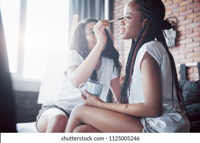 Two beautiful african girl in sleepwear smiling sitting on bed at home woke up in the morning on a sunny day. Women share make-up and tidy themselves up