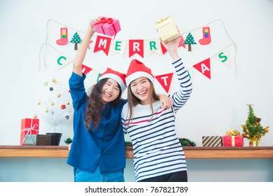 Two beautiful asian girl frind holding christmas gift box and smile in party at home