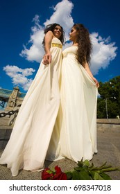 Two beautiful asian girls in white dresses in Greek style posing in the park