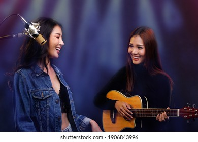 Two Beautiful Asian Singer Women sing song and play guitar on cafe stage, Lgbt lovers express feeling of Love during Concert session, smile and look at each other