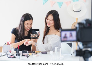 Two beautiful asian woman blogger showing how to make up and use cosmetics. In front of the camera to recording vlog video live streaming at home.Business online influencer on social media concept.