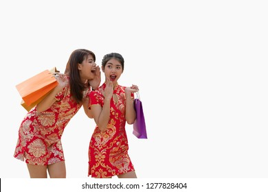 Two beautiful asian women, hold shopping bags, one whisper in friend's ear who has excited face, Both are enjoy celebrating Chinese New Year, dress in red qipao/cheongsam.Isolated on white background.