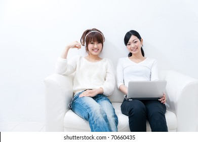 two beautiful asian women relaxing on the sofa