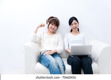 two beautiful asian women relaxing on the sofa