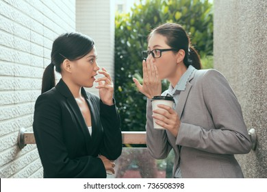 two beautiful Asian women talking about office gossip and feel shocked at rest time outdoor of the studio.