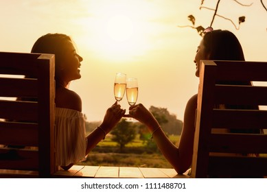 Two beautiful asian women toss white wine of champange in with warm sunset light
