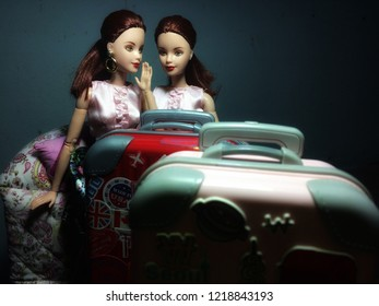 Two beautiful Barbie dolls are whispering some secret. They're sitting on floral sofa. The foreground is blurred luggage branded KITKAT.